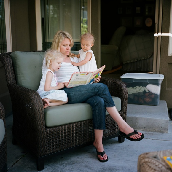 Mother reading books to two kids