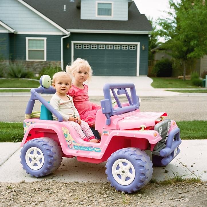 2 girls in a hot wheels jeep